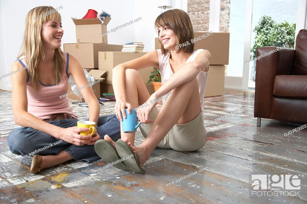 Stock Photo: Two women sitting on hardwood floor with mugs and cardboard boxes smiling.