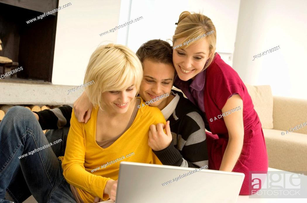 Stock Photo: Young man with two young women looking at a laptop and smiling.