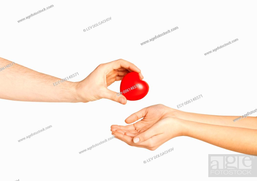 Stock Photo: love, relationship, charity and medicine concept - man hand giving red heart to woman.