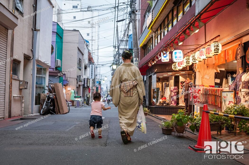 Stock Photo: Woman with baby walking in the streets of Tokyo, Japan, Asia.
