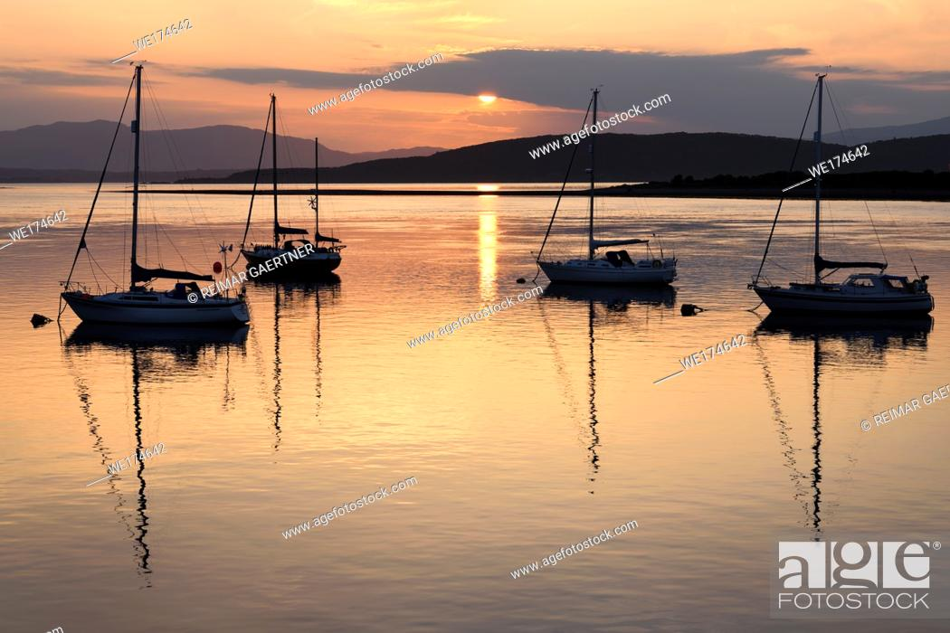 Stock Photo: Red sky at sunset reflecting on the water of Ardmucknish Bay at North Connel and Oban Airport with sailboats in silhouette.