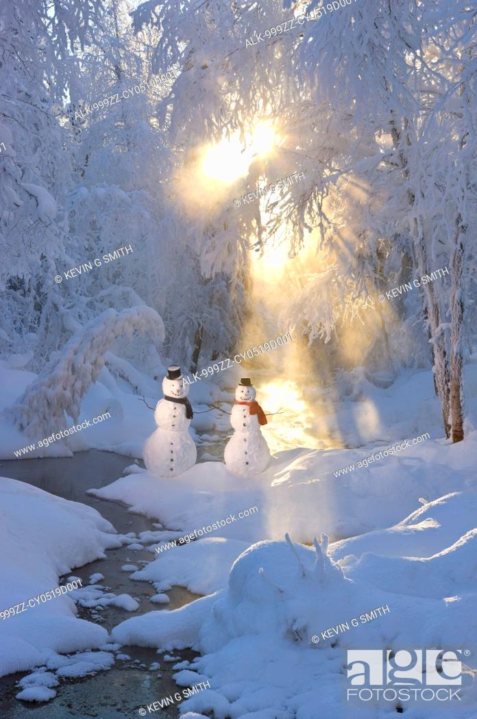 Stock Photo: Snowman couple standing next to a stream with sunrays shining through fog and hoar frosted trees in the background, Russian Jack Springs Park, Anchorage.