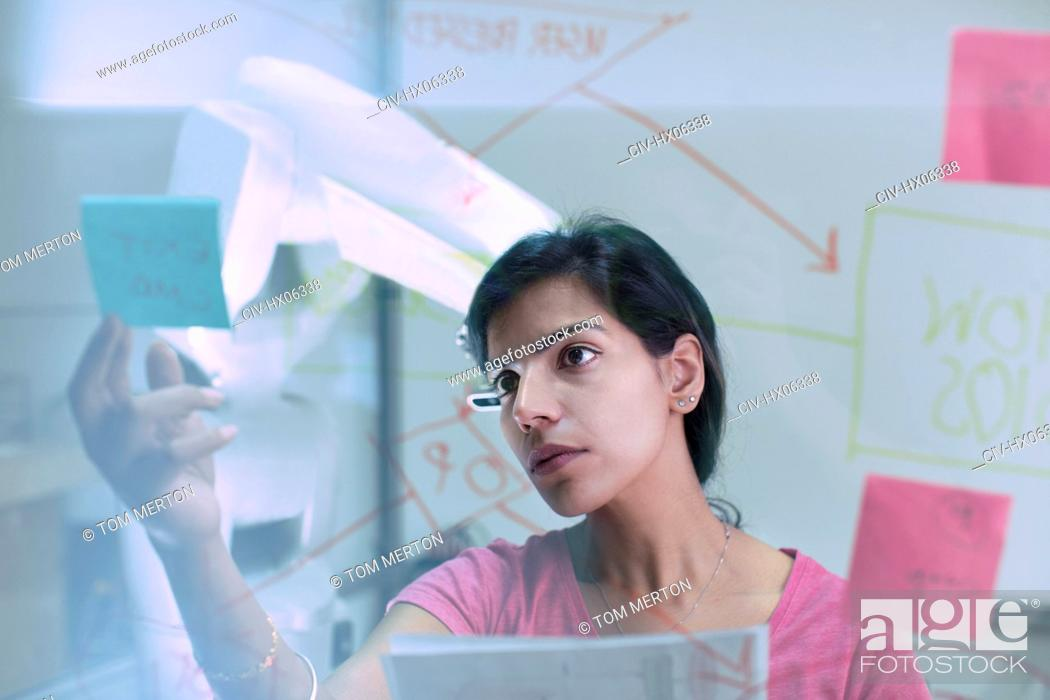 Stock Photo: Businesswoman reviewing adhesive notes and flow chart, planning in office.