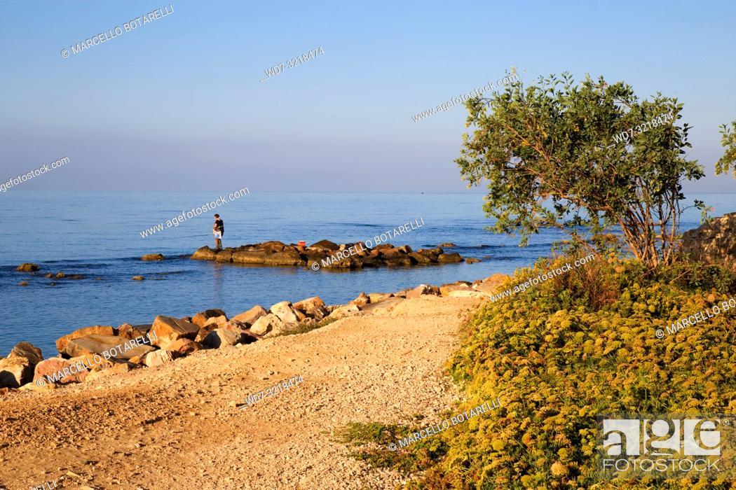 Stock Photo: rocks by the sea of Santa Severa, fisherman on the rocks, near Rome, Italy.