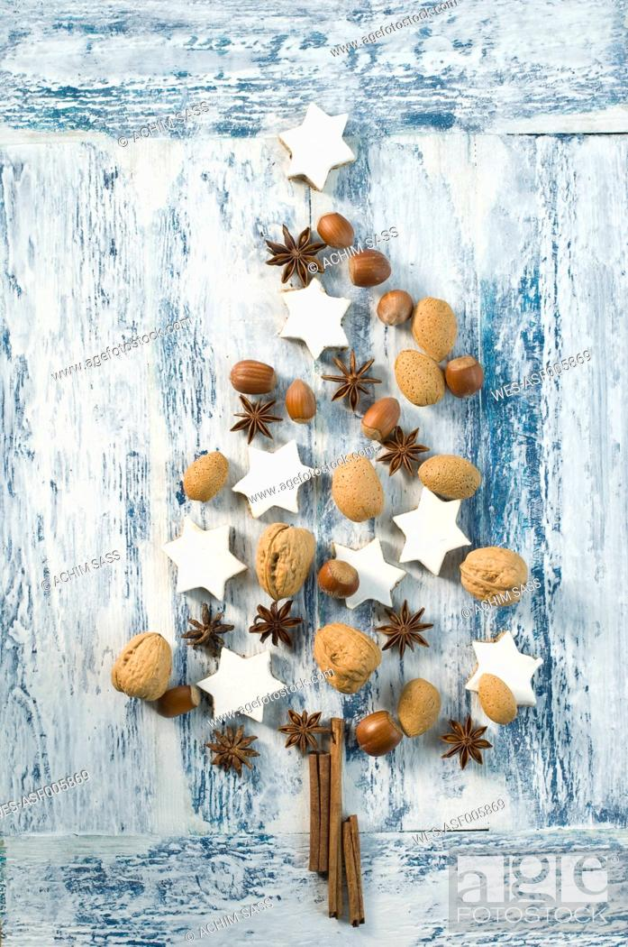 Photo de stock: Cinnamon stars, cinnamon sticks, star anise and nuts shaped like a Christmas tree.