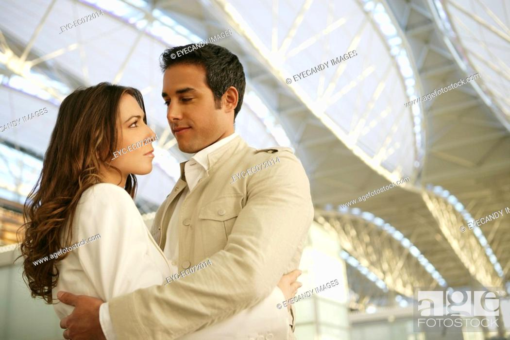 Stock Photo: Young couple hugging in airport.