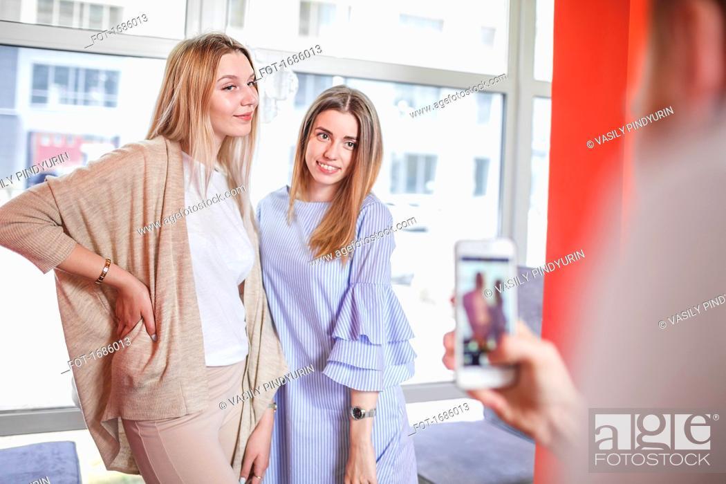 Imagen: Man photographing female friends standing at restaurant.