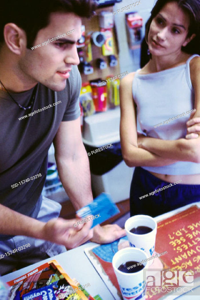 Stock Photo: Young couple standing at a store counter holding a credit card.