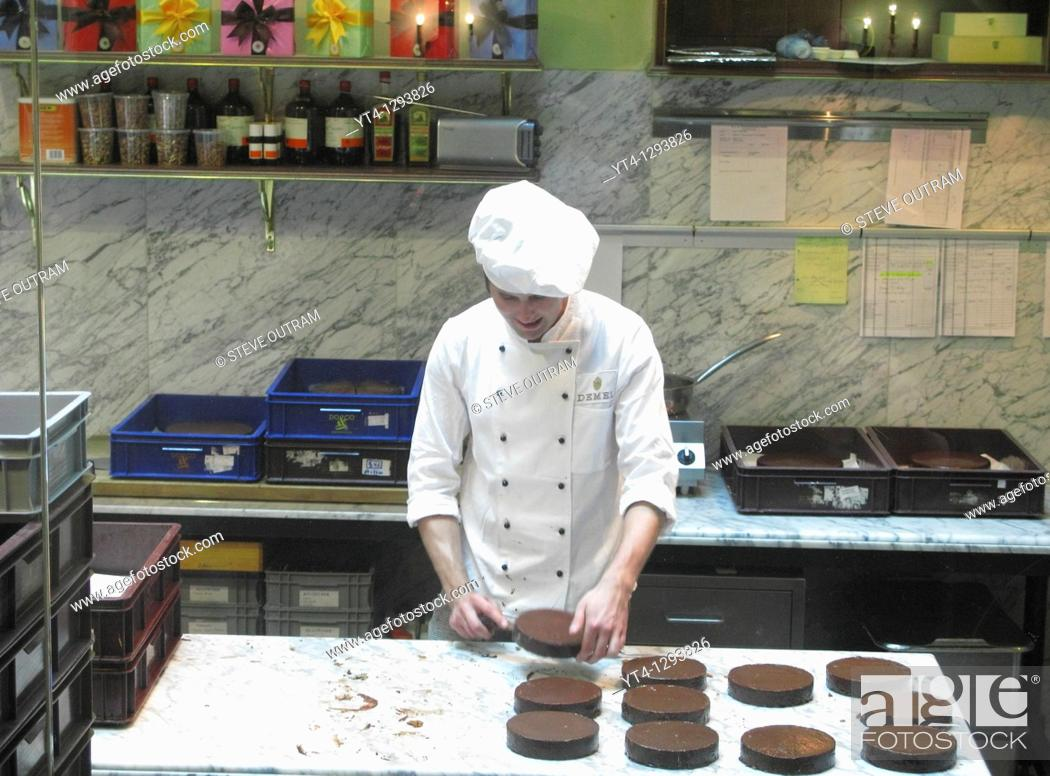 Stock Photo: Young Chef preparing Sacher Torte Cakes in the kitchen of Cafe Demel, Vienna, Austria.