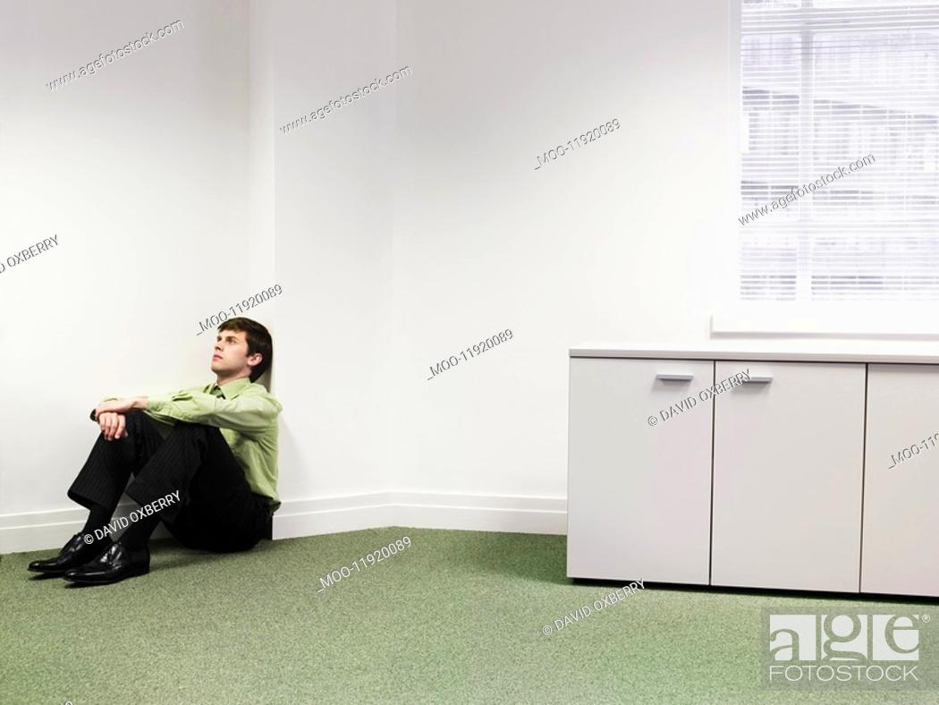 Stock Photo: Businessman sitting on floor in corner of office.