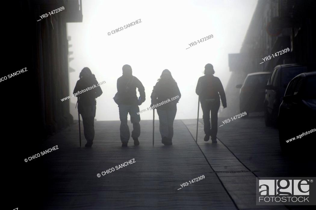 Stock Photo: Pilgrims walk through the early morning fog in Portomarin town, Galicia region, in the French Way that leads to Santiago de Compostela, Spain.