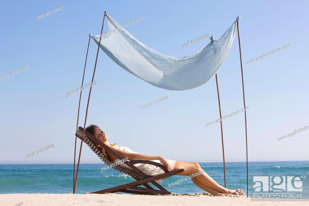 Stock Photo: Woman resting in a deck chair under a canopy.