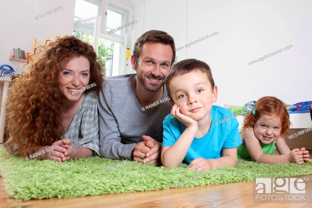 Stock Photo: Germany, Berlin, Family lying on floor, smiling, portrait.