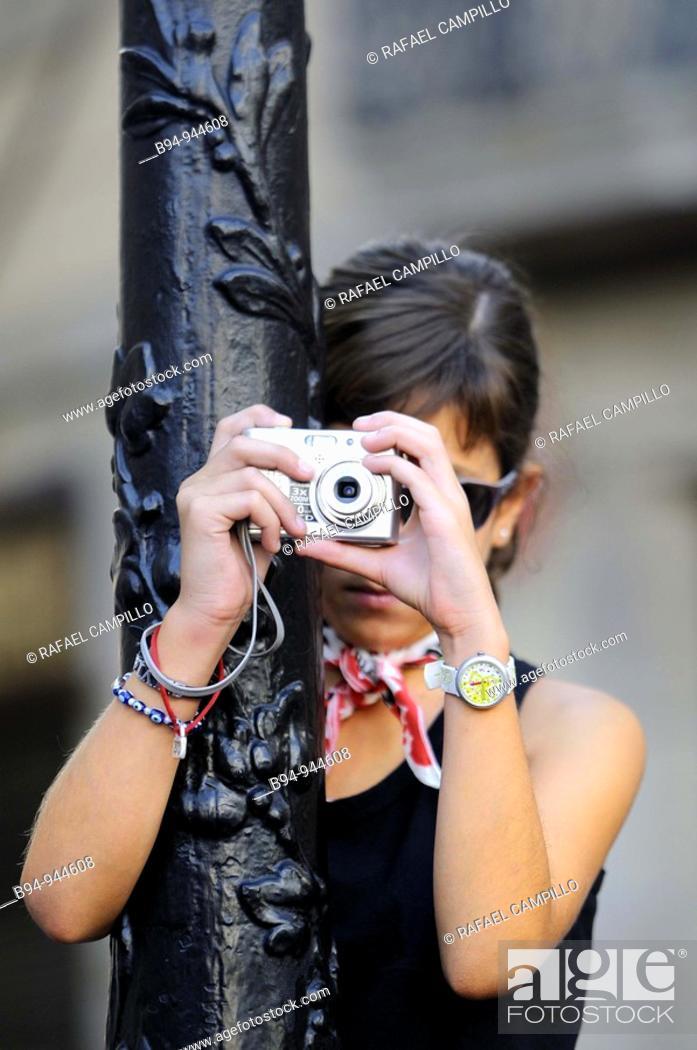 Stock Photo: Girl taking pictures in Plaça Sant Jaume, La Merce feast, Barcelona, Catalonia, Spain.