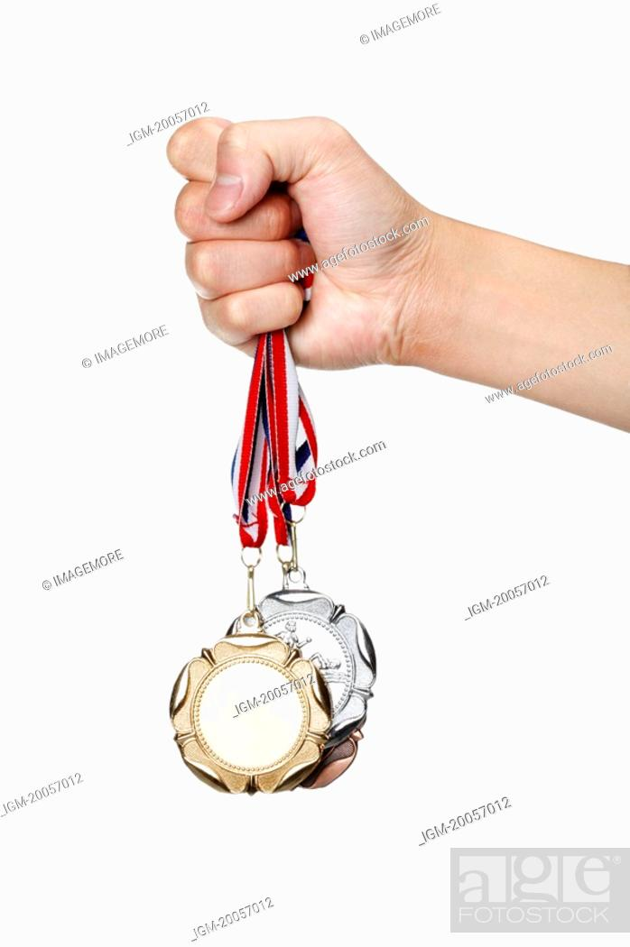 Stock Photo: Human hand holding medal.