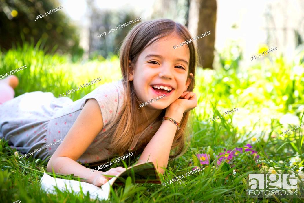 Stock Photo: Smiling girl lying on meadow, reading a book.