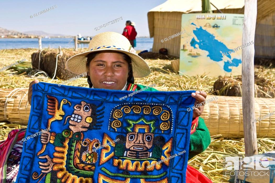 Stock Photo: Portrait of a young woman showing a decorated blanket, Peru.