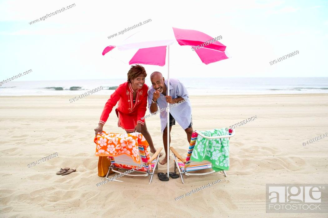 Stock Photo: Couple pointing and laughing under beach umbrella.