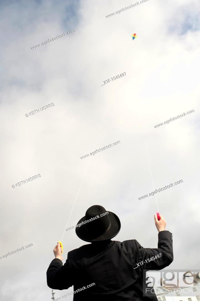 Stock Photo: Flying a kite: Orthodox Hassidic jews on summer holiday on the beach at Aberystwyth Wales UK.