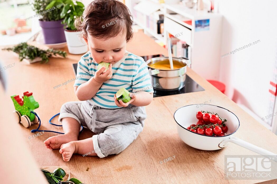 Stock Photo: Baby girl sitting on kitchen counter, eating cucumber.