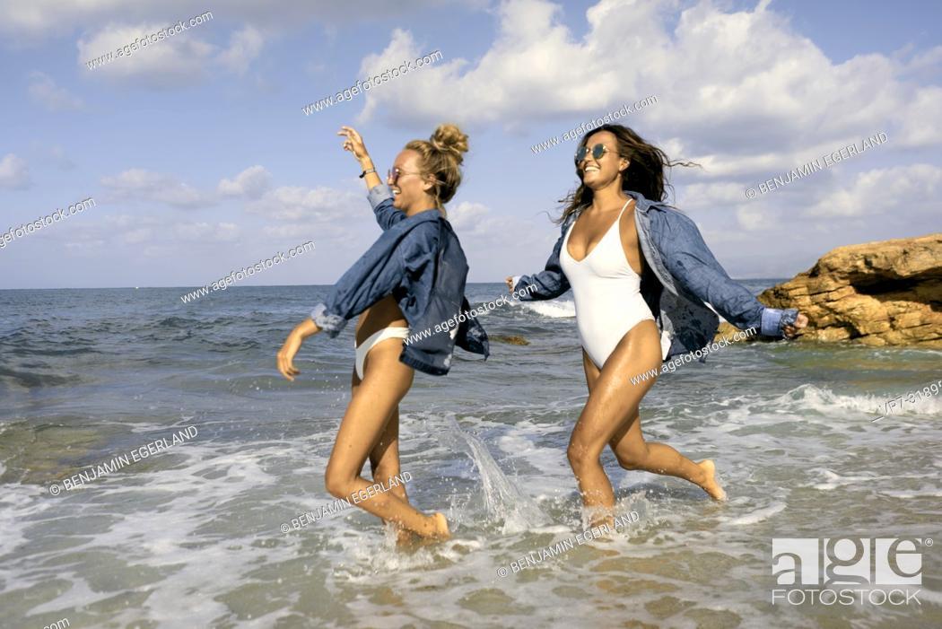 Imagen: Two women running in sea water at beach, Chersonissos, Crete, Greece.