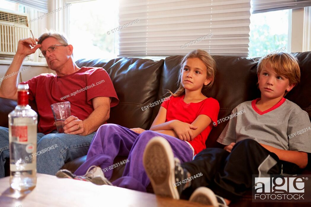 Stock Photo: Father Sits On Sofa With Children Smoking And Drinking.