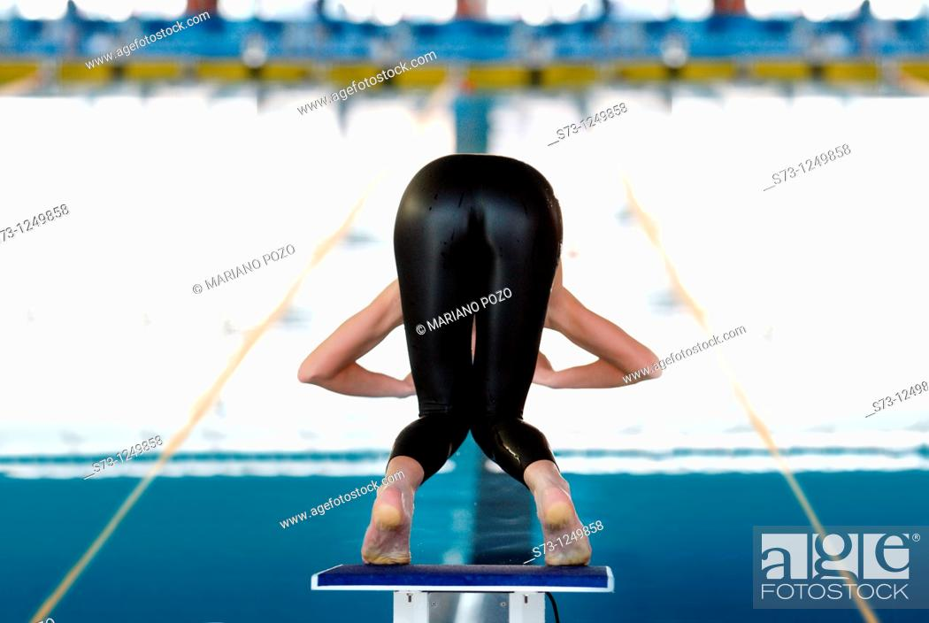 Stock Photo: Young woman about to dive in swimming competition.