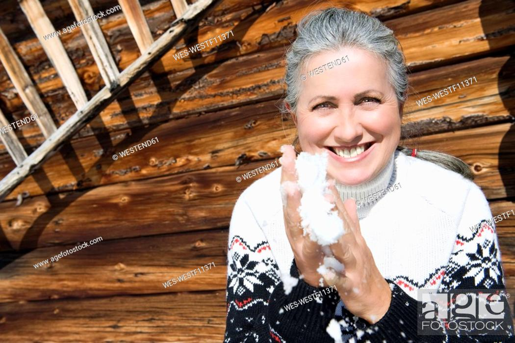 Stock Photo: Italy, South Tyrol, Seiseralm, Senior woman holding snow in hands, smiling, portrait.
