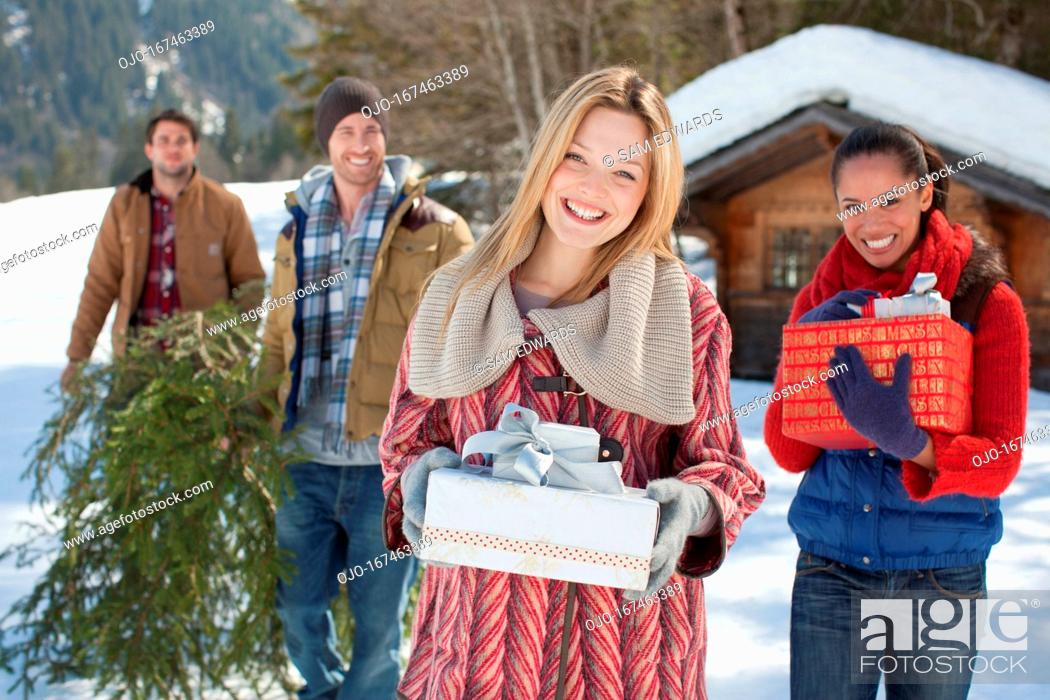 Stock Photo: Portrait of smiling couples with fresh cut Christmas tree and gifts in snow.