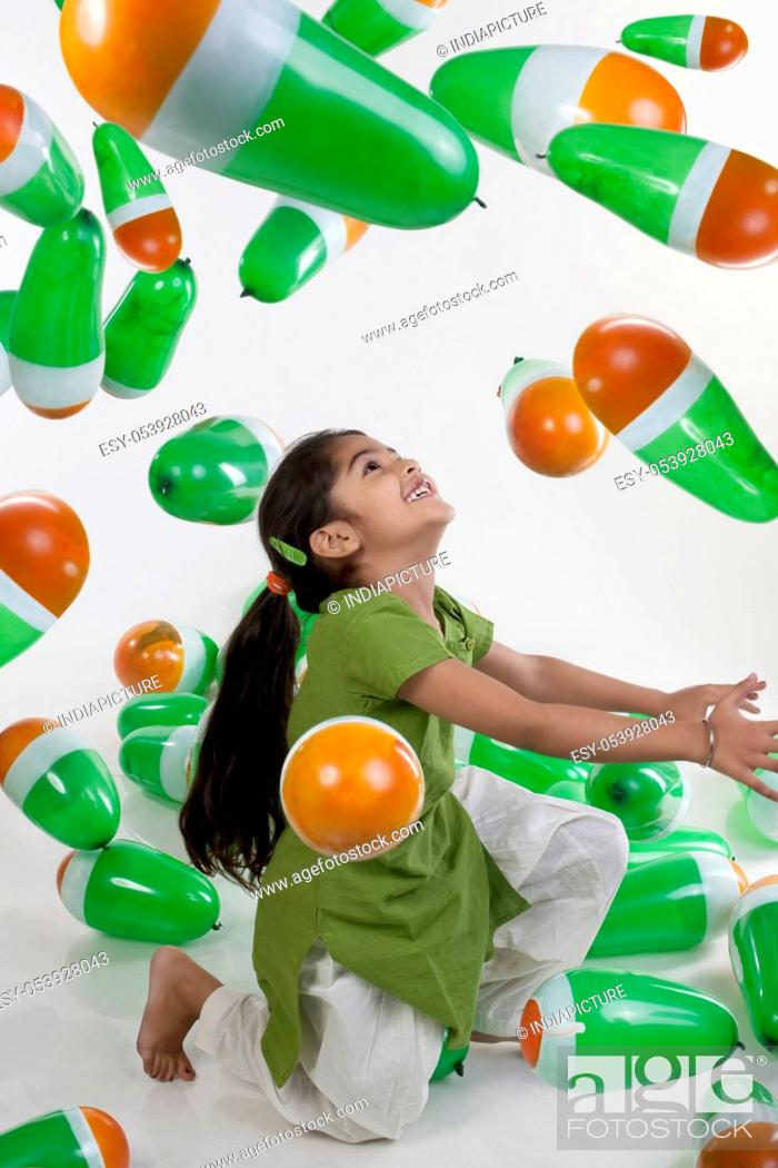 Stock Photo: Girl playing with balloons.