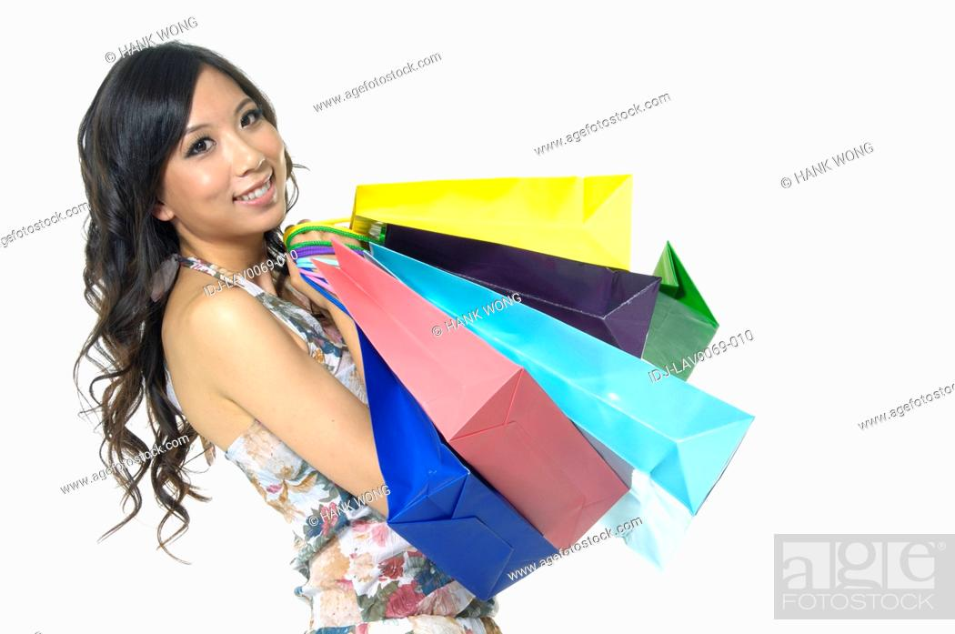 Stock Photo: Woman carrying shopping bags and smiling.