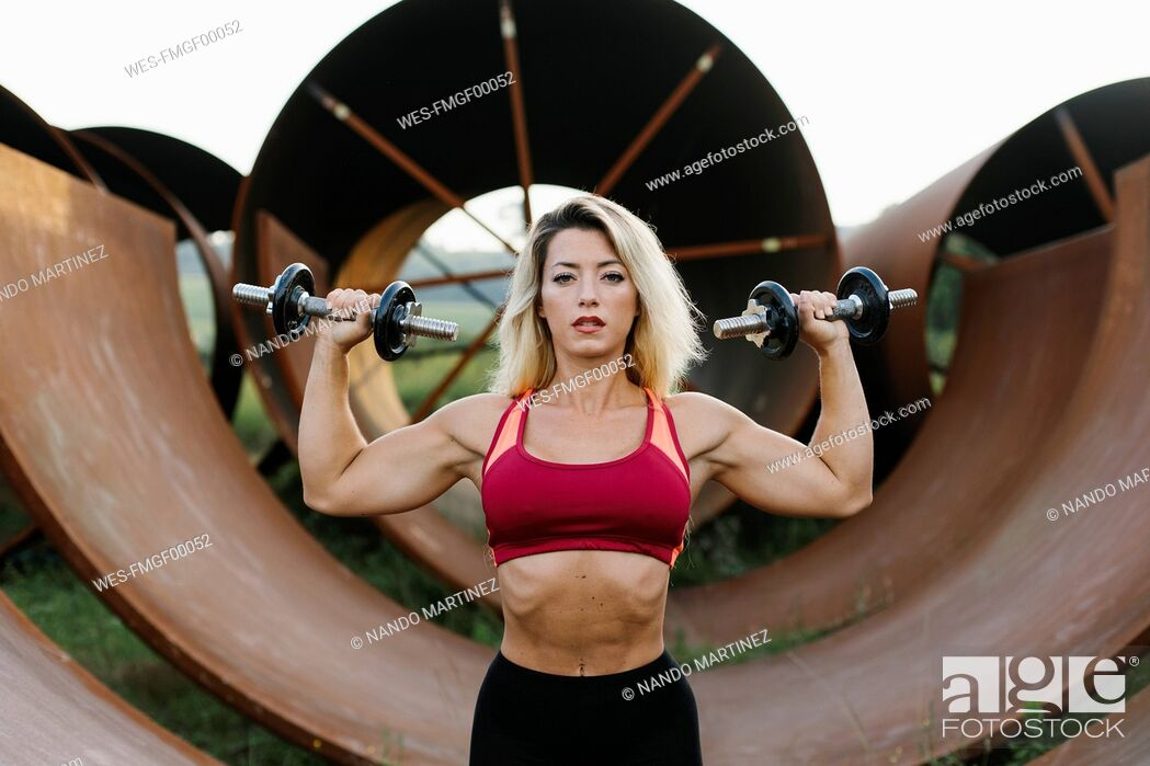 Stock Photo: Athletic woman doing weight workout at industrial site.