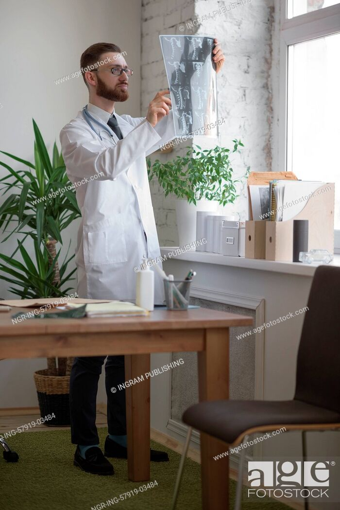 Stock Photo: Doctor working with ct scan at hos workplace.
