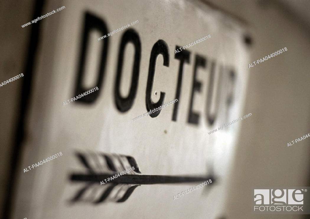 Stock Photo: 'Doctor' text in French on sign with arrow, close-up.