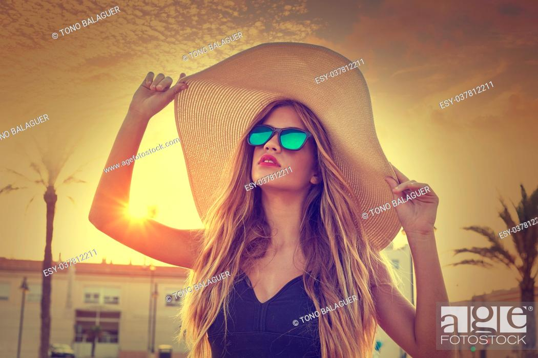 Stock Photo: Blond teen girl sunglasses and pamela sun hat at palm tree sunset filtered image.