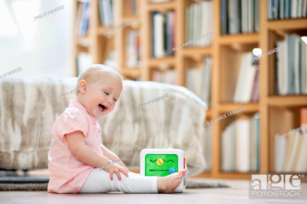 Stock Photo: Baby girl playing with a musical block toy.