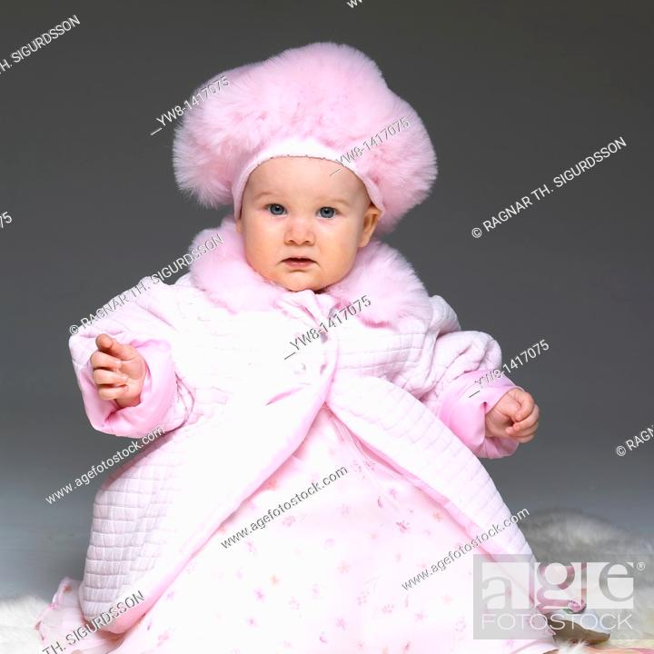 Stock Photo: Baby girl in pink dress, coat and hat.