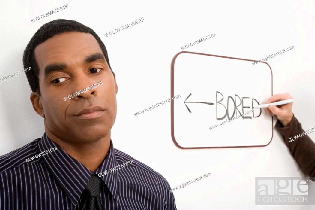 Stock Photo: Businessman thinking with a person's hand writing on a whiteboard.