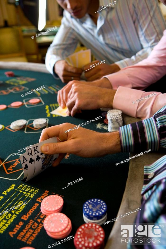 Stock Photo: Young men gambling at poker table in casino, section.