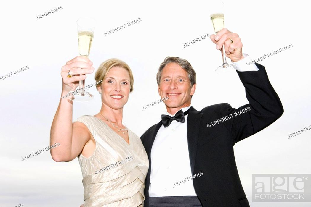 Stock Photo: Portrait of couple in eveningwear holding champagne flutes.