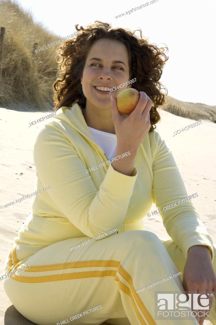 Stock Photo: Woman eating apple at beach.