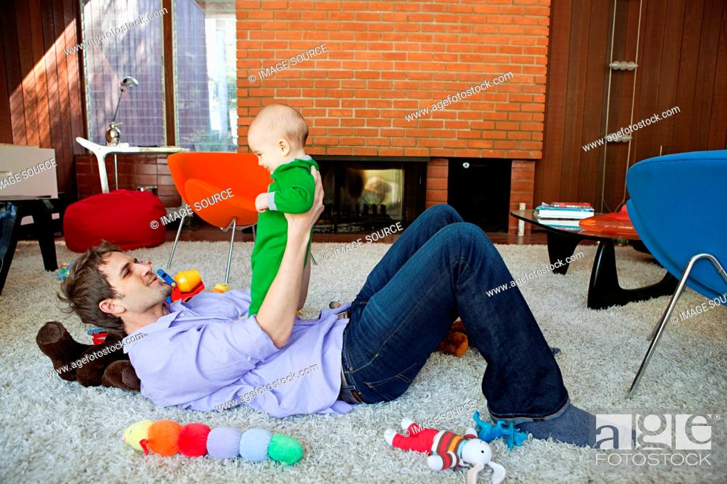 Stock Photo: Father playing with baby son in living room.
