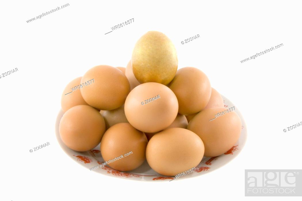 Stock Photo: One golden and many ordinary easter rural eggs lying in white porcelain plate with a red ornament.
