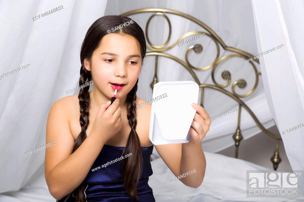 Stock Photo: little girl sitting on a bed looks in the mirror and painting lips like her mom.