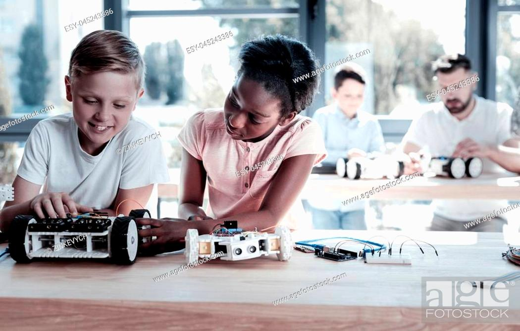Stock Photo: Always work as a team. Smart preteen children sitting next to each other and focusing their attention on their new robotic machines while spending their leisure.
