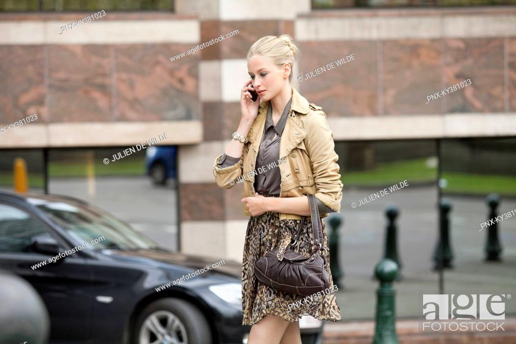 Stock Photo: Woman crossing the road while talking on a mobile phone.