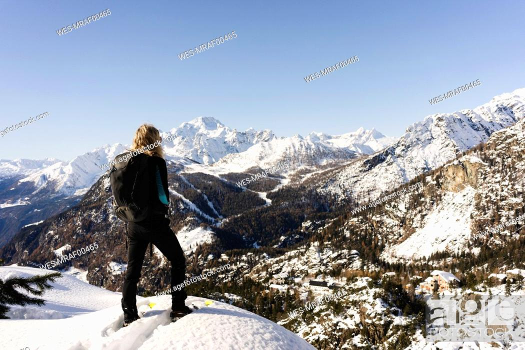 Stock Photo: Woman stanging with snowshoes on viewpoint, Valmalenco, Italy.