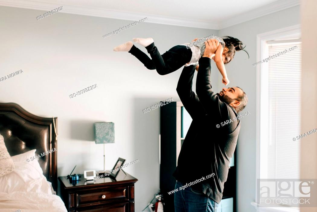 Stock Photo: Girl being held up by father in bedroom.