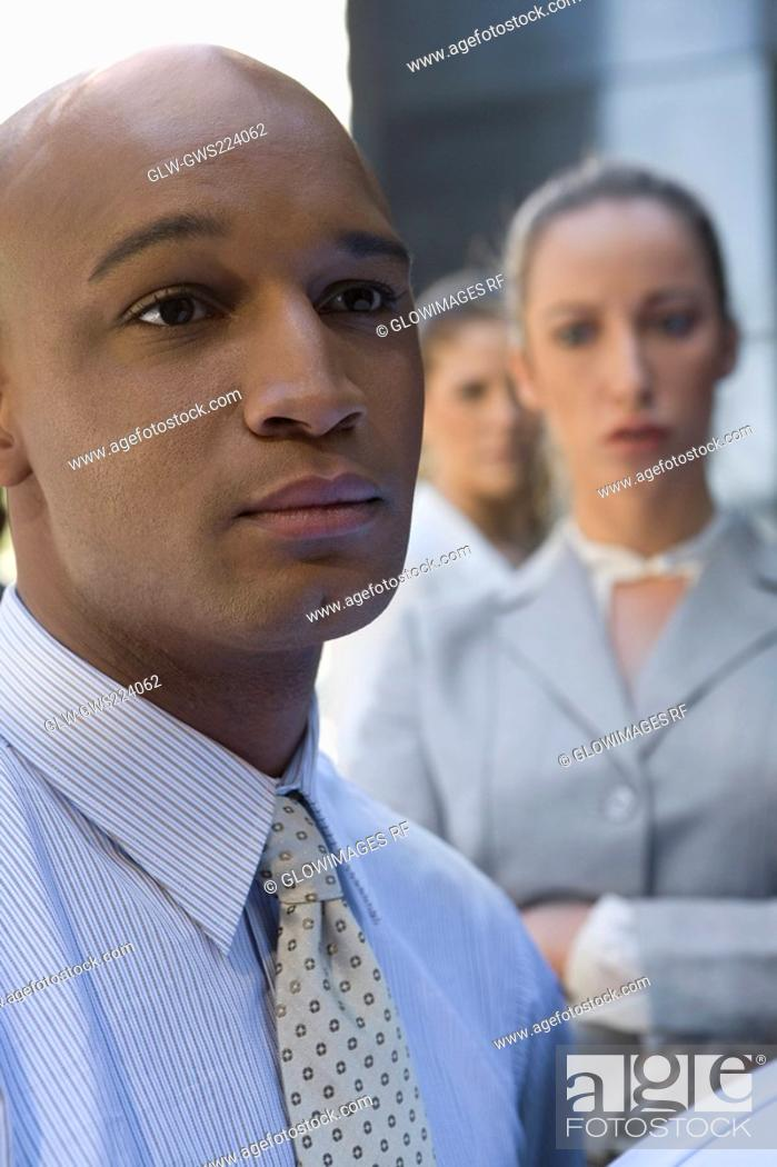 Stock Photo: Close-up of a businessman looking serious with two businesswomen in the background.