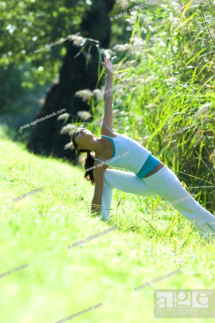 Stock Photo: Young woman exercising in park.